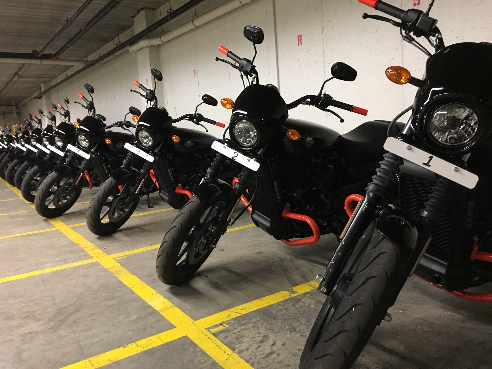 A lineup of black and orange motorcycles.