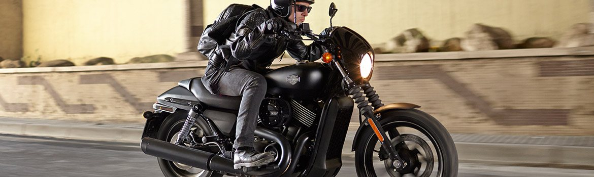 Man wearing black leather races a black motorcycle.