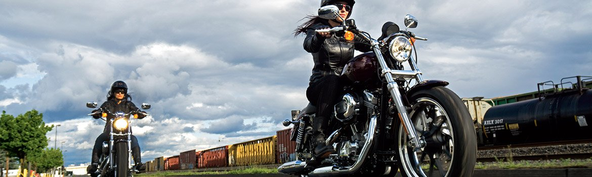 Two women ride motorcycles while racing a train.