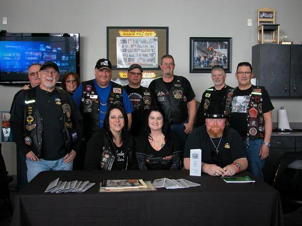 A group of smiling riders pose in their HOG Chapter vests.